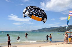 Phuket, Thailand: Paragliding at Patong Beach. Tourist and her Thai flyer lift off for a parasailing ride over the Andaman Sea Stock Photo