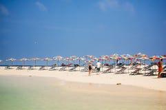 Phuket Thailand - 2009: Strandstolar och färgglade paraplyer fodrar stranden royaltyfri foto