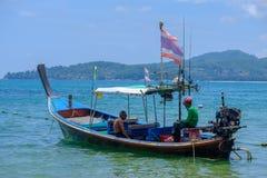 Phuket thailand 08/05/2018 - Vissers die in zijn lange staartboot zitten stock foto