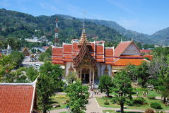 Phuket, Thailand: Wat Chalong. The grand Ubosot Sanctuary Hall with its steeply pitched orange tile roofs, ornate tympaum, gilded spire, and gardens at Wat Royalty Free Stock Images
