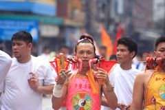 Phuket Vegetarian Festival. PHUKET, THAILAND - OCTOBER 19: An unidentified devotee of a Chinese shrine gets pierced on his cheek to take part in the 2012 stock images
