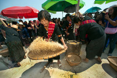 Phutai minority woman poundind and winnowing rice. KALASIN,THAILAND-MARCH 9 : Group of unidentified Phutai minority senior woman competitive pounding and Stock Photography