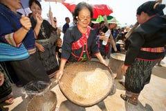 Phutai minority woman pounding and winnowing rice. Royalty Free Stock Image