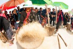Phutai minority woman pounding and winnowing rice. Stock Image