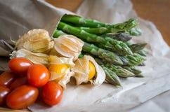 Physalis, asperge, tomaat op papier Royalty-vrije Stock Afbeeldingen