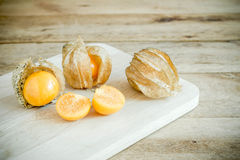Physalis, or Cape Gooseberry fruit over old wood background. Royalty Free Stock Photography