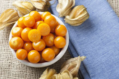 Physalis Fruit in Bowl. Physalis fruit with one cut in half in bowl on blue napkin and burlap Stock Photos