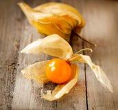 Physalis fruits. Physalis fruit over wooden background stock photos