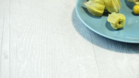 Physalis fruits. On blue ceramic plate and a wooden table stock video