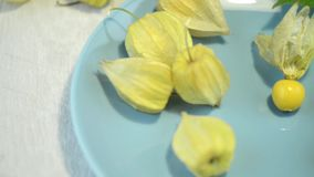 Physalis fruits. On blue ceramic plate and a wooden table stock video footage