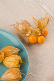 Physalis fruits. On blue ceramic plate and a wooden table Royalty Free Stock Photography
