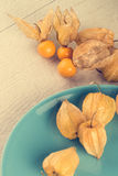Physalis fruits. On blue ceramic plate and a wooden table Royalty Free Stock Photos