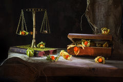 Physalis fruits escape from a jewelery box to a brass scale, still life metaphor on a rustic wooden table in front of a dark. Physalis fruits escape from a royalty free stock image