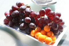 Physalis and grapes. Sweet grapes and physalis together placed on white plate Stock Photo