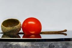 Physalisbeere und die Überreste der Eichel auf einem Spiegel tauchen auf Stockfotos