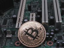 Physical bitcoin on computer motherboard. A physical bitcoin on a computer motherboard Royalty Free Stock Photo