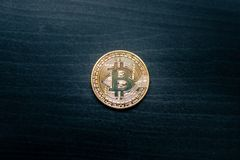 A physical bitcoin in the middle of a dark wooden background stock images