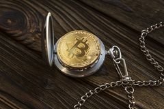The physical bitcoin and vintage pocket watch shows that time is running out. Old-fashioned open clock bokoyunov lying background of a wooden table surface Royalty Free Stock Photo