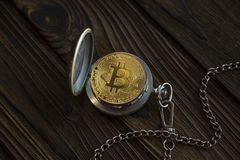 The physical bitcoin and vintage pocket watch shows that time is running out. Old-fashioned open clock bokoyunov lying background of a wooden table surface Stock Photos