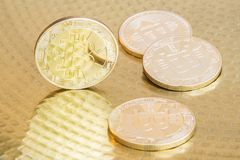 Physical bitcoins on golden background. Physical bitcoin coins on golden background Royalty Free Stock Images
