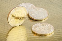 Physical bitcoins on golden background. Physical bitcoin coins on golden background Stock Image