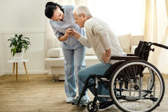 Nice aged man trying to get up. Physical disability. Nice sad aged men holding a caregivers hand and trying to get up while having a physical disability Royalty Free Stock Photo