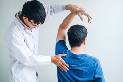 Physical Doctor consulting with patient About Shoulder muscule pain problems Physical therapy diagnosing concept.  stock photo