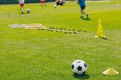 Physical Education Class. Soccer Training Session on the Grass Sports Field. Football Training Equipment. Traditional Soccer Ball, Speed and Agility Training royalty free stock photography