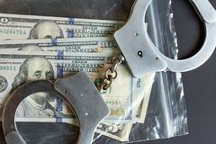 Currency in a plastic package and handcuffs. royalty free stock photo