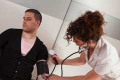 Physical examination. Young female doctor measuring blood pressure Stock Photos