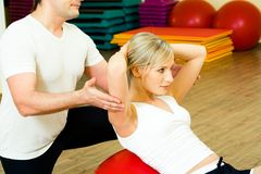Physical exercise. Photo of woman doing physical exercise with man near by Stock Photography