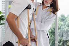 Physical female doctor helping patient with crutches in hospital office.  stock photography