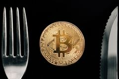 Physical Golden Crytocurrency Coin between fork and knive. Currency of the future Stock Photos