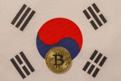 Korean flag with bitcoin, physical metal coin. Physical, metal cryptocurrency coin on textile Korean flag royalty free stock photography
