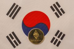 Korean flag with bitcoin, physical metal coin. Physical, metal cryptocurrency coin on textile Korean flag royalty free stock image