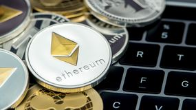Physical metal silver Ethereum currency on notebook computer keyboard ETH. Physical metal silver Ethereum currency, notebook computer keyboard. Worldwide virtual stock photos