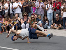 Physical performance of a breakdancer in the street. AURILLAC, FRANCE, AUGUST 22: Spectators look at a young breakdancer in the street as part of the Aurillac royalty free stock photo