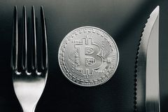 Physical silver Crytocurrency Coin between fork and knive. Bitcoin is currency of the future Stock Photos