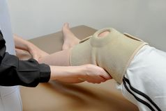 Physical therapist applying knee support to patient knee,rehabil Royalty Free Stock Photo