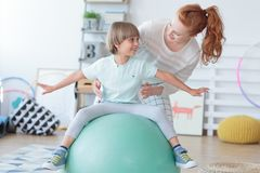 Physical therapist assisting little boy. Sitting on gym ball during rehabilitation in children hospital Stock Photography