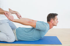 Physical therapist assisting man with stretching exercises. Side view of a physical therapist assisting young men with stretching exercises in the gym hospital Stock Photos