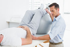 Physical therapist assisting man with yoga ball Royalty Free Stock Photography
