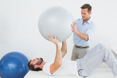 Physical therapist assisting man with yoga ball stock image