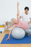 Physical therapist assisting senior woman with yoga ball Royalty Free Stock Photography