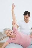Physical therapist assisting senior woman with yoga ball Royalty Free Stock Photos