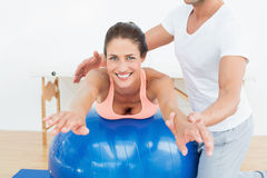 Physical therapist assisting woman with yoga ball Royalty Free Stock Images