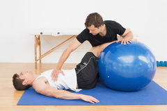 Physical therapist assisting young man with yoga ball Stock Photo