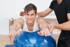 Physical therapist assisting young man with yoga ball Stock Images