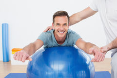 Physical therapist assisting young man with yoga ball Royalty Free Stock Photos