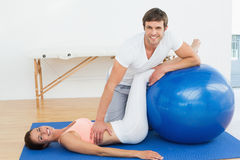Physical therapist assisting young woman with yoga ball Stock Photography